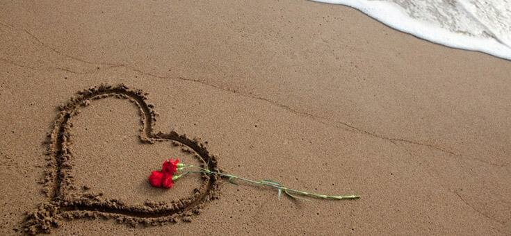 Heart drawn in sand with a flower over
